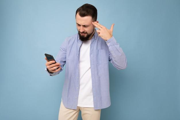 Wütend verärgerter hübscher junger brünetter unrasierter mann mit bart, der ein stilvolles weißes t-shirt und ein blaues hemd trägt, isoliert auf blauem hintergrund mit leerem raum in der hand und mit dem telefon, das nachrichten online liest