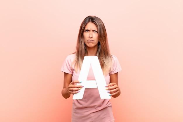 Wütend, wütend, nicht einverstanden, den buchstaben a des alphabets halten, um ein wort oder einen satz zu bilden.