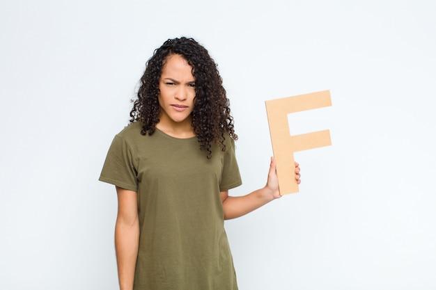 Wütend, wütend, nicht einverstanden, den buchstaben f des alphabets haltend, um ein wort oder einen satz zu bilden.