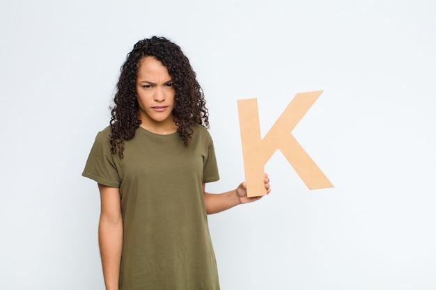 Wütend, wütend, nicht einverstanden, den buchstaben k des alphabets haltend, um ein wort oder einen satz zu bilden.