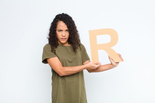 Wütend, wütend, nicht einverstanden, den buchstaben r des alphabets haltend, um ein wort oder einen satz zu bilden.