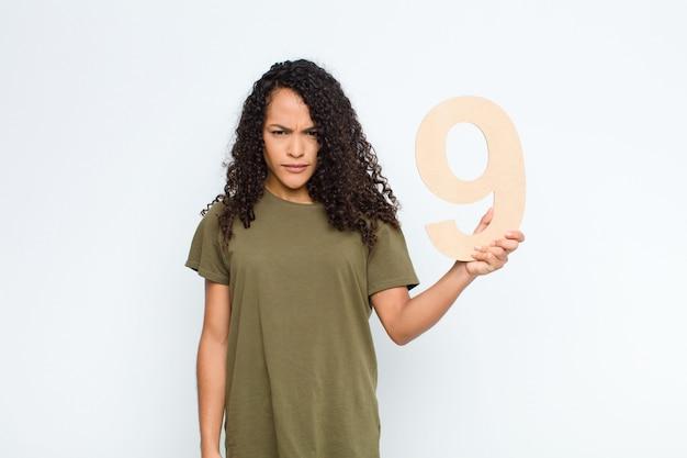 Wütend, wütend, nicht einverstanden, eine nummer 9 in der hand.