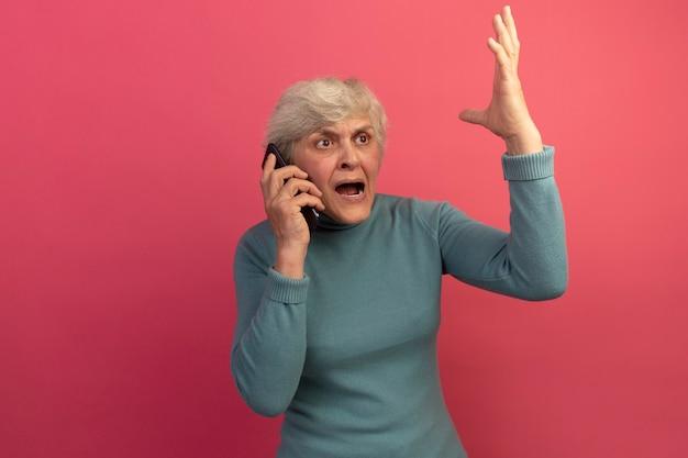 Wütende alte frau mit blauem rollkragenpullover, die am telefon spricht und auf die seite blickt, die die hand isoliert auf rosa wand mit kopierraum hebt