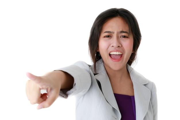 Wütende asiatische frau, die mit dem finger wegzeigt und auf weißem isoliertem hintergrund im studio schreit.