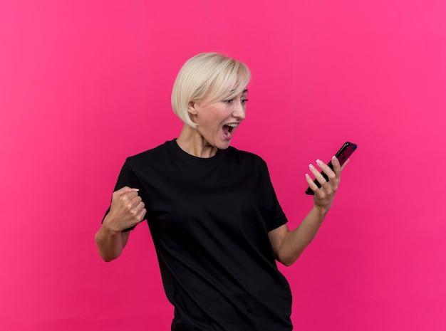 Wütende blonde frau mittleren alters, die handy-geballte faust hält und betrachtet, lokalisiert auf rosa wand