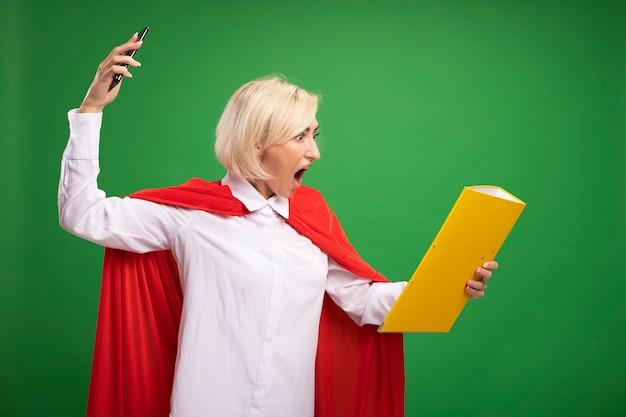 Wütende blonde superheldin mittleren alters in rotem umhang, die am telefon spricht und auf einen ordner schaut, der das handy schreiend isoliert auf grüner wand hochhebt