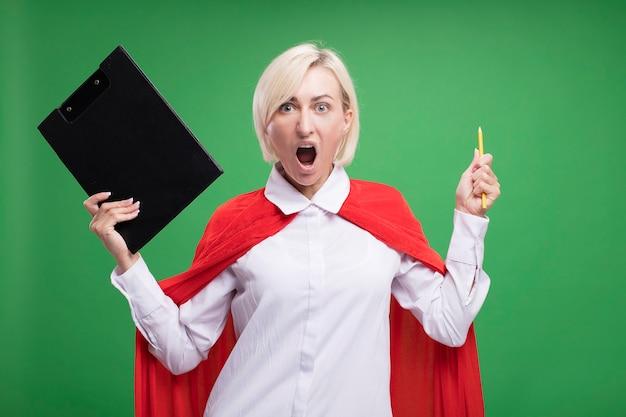 Wütende blonde superheldin mittleren alters in rotem umhang, die zwischenablage und bleistift hält und nach vorne schreit, isoliert auf grüner wand