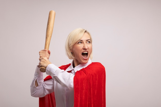 Wütende blonde superheldin mittleren alters in rotem umhang hebt baseballschläger und schaut auf die seite, die isoliert auf weißer wand mit kopienraum schreit