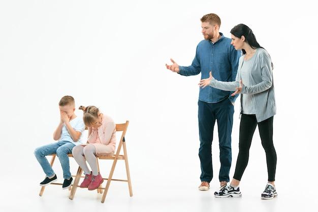 Wütende eltern schimpfen mit ihren kindern - sohn und tochter zu hause. studioaufnahme der emotionalen familie. menschliche emotionen, kindheit, probleme, konflikte, häusliches leben, beziehungskonzept