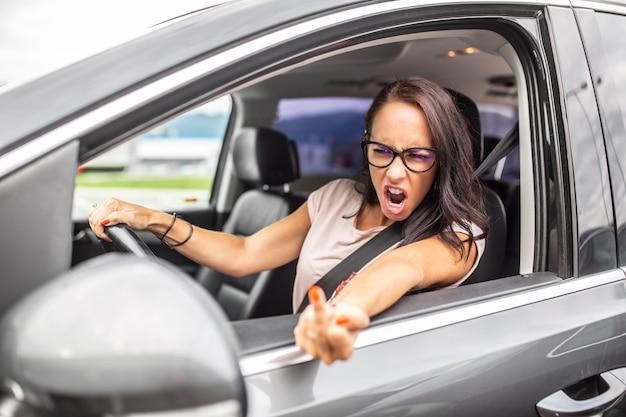 Wütende fahrerin zeigt während eines staus zur hauptverkehrszeit den mittelfinger in einen rückspiegel.