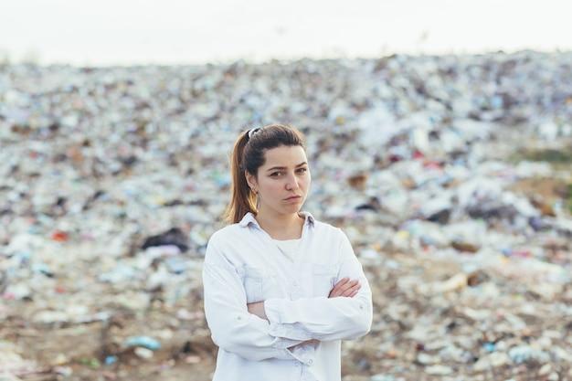 Wütende frau, die auf einer mülldeponie steht, unzufrieden mit dem ausmaß der umweltverschmutzung, die in die kamera schaut