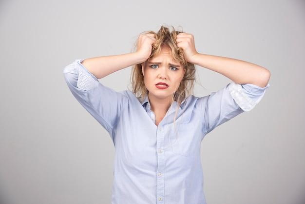 Wütende frau, die ihr haar auf grauer oberfläche zieht