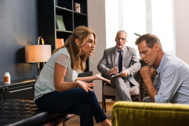 Wütende frau, die ihren verzweifelten ehemann anschreit, während sie im büro des psychologen vor ihm sitzt