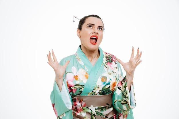 Wütende frau im traditionellen japanischen kimono, die die hände hebt und wild schreit auf weiß