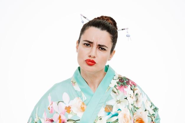 Wütende frau im traditionellen japanischen kimono mit stirnrunzelndem gesicht auf weiß