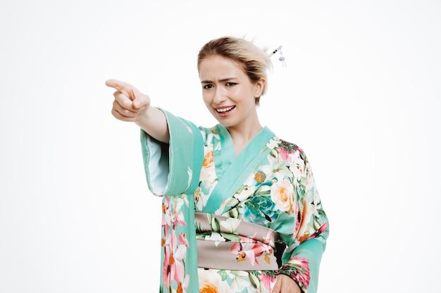 Wütende frau im traditionellen japanischen kimono zeigt mit dem zeigefinger zur seite auf weiß