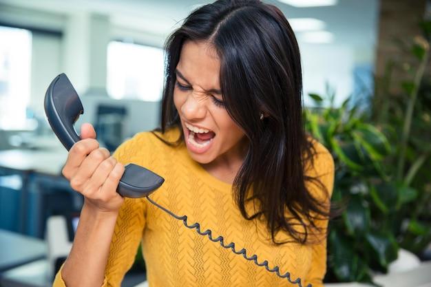 Wütende geschäftsfrau, die im büro am telefon schreit