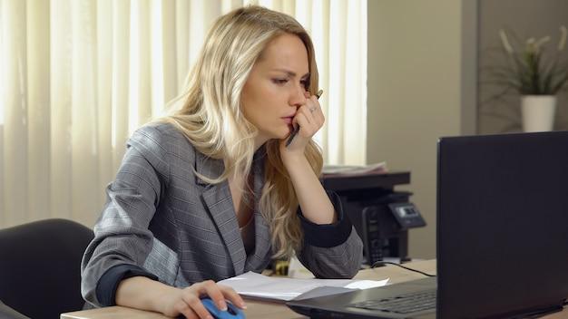 Wütende geschäftsfrau im anzug arbeitet am computer im büro.