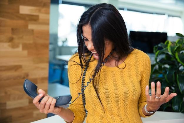 Wütende geschäftsfrau schreit im büro am telefon