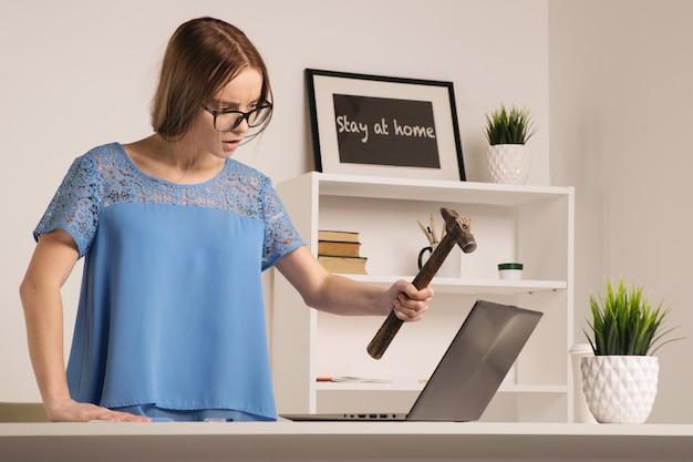 Wütende geschäftsfrau wurde verrückt nach hammer und laptop