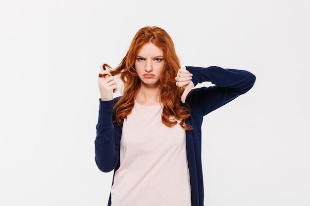 Wütende hübsche rothaarige dame, die wegen der haare daumen nach unten zeigt.