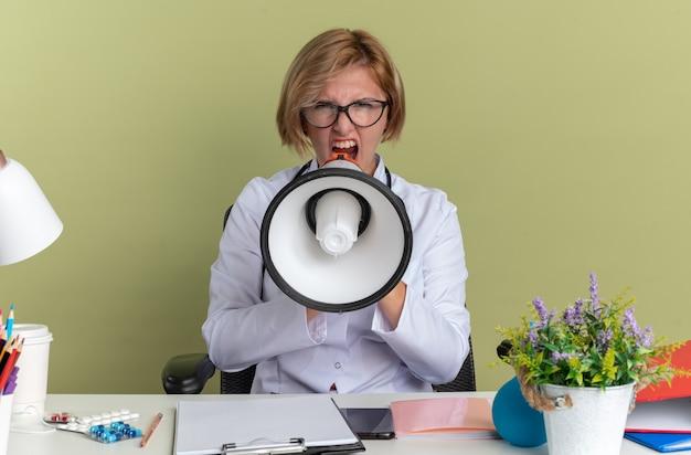 Wütende junge ärztin, die ein medizinisches gewand mit brille und stethoskop trägt, sitzt am tisch mit medizinischen werkzeugen und spricht über lautsprecher, die auf olivgrüner wand isoliert sind
