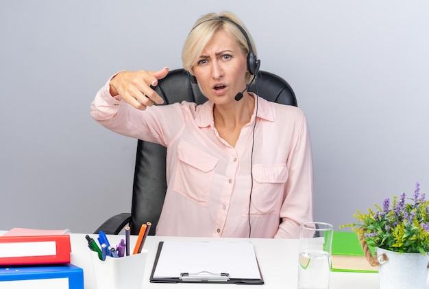 Wütende junge callcenter-betreiberin mit headset am tisch sitzend mit bürowerkzeugen zeigt auf die kamera isoliert auf weißer wand