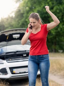 Wütende junge frau, die wegen des kaputten autos auf der landstraße im handy schreit