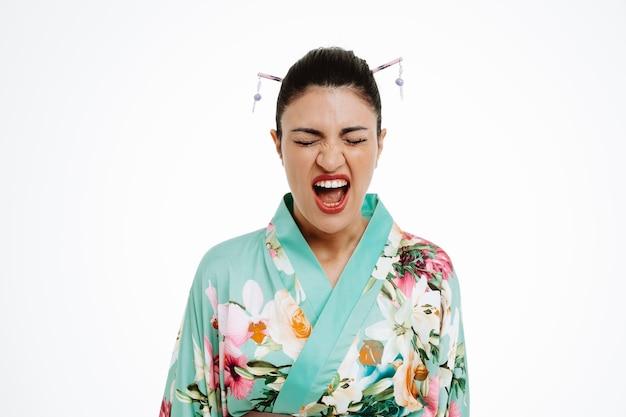 Wütende junge geisha-frau im traditionellen japanischen kimono, die mit verärgertem ausdruck schreit, der über weißer wand steht
