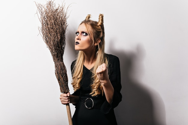 Wütende junge hexe mit besen hebt die faust. foto des blonden mädchens mit dunklem make-up trägt halloween-kostüm.