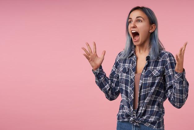Wütende junge hübsche frau mit kurzen blauen haaren, die emotional ihre hände heben und den mund weit offen halten, während sie wütend schreien, isoliert auf rosa