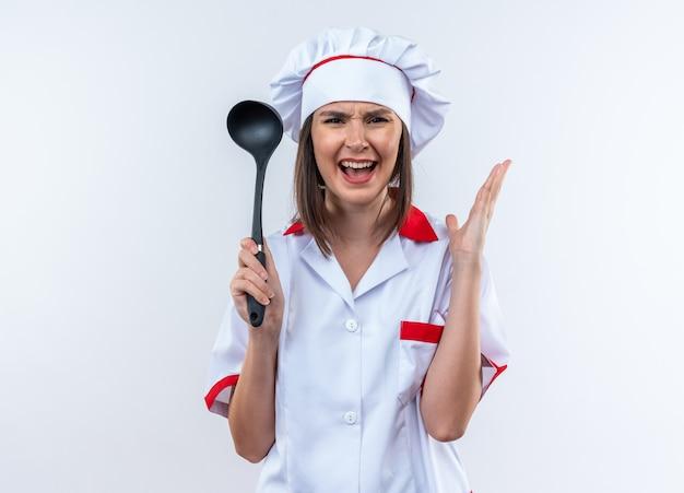 Wütende junge köchin in kochuniform mit schöpfkelle isoliert auf weißem hintergrund