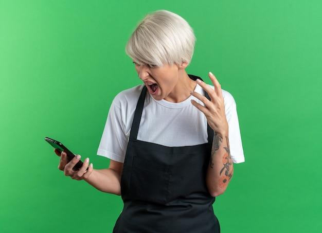 Wütende junge schöne friseurin in uniform, die das telefon isoliert auf grüner wand hält und betrachtet