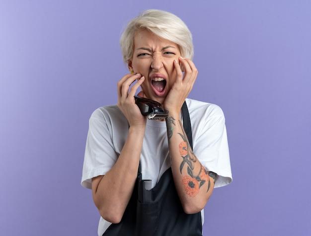 Wütende junge schöne friseurin in uniform, die haarschneidemaschinen hält, die hände auf die wangen legen, isoliert auf blauer wand
