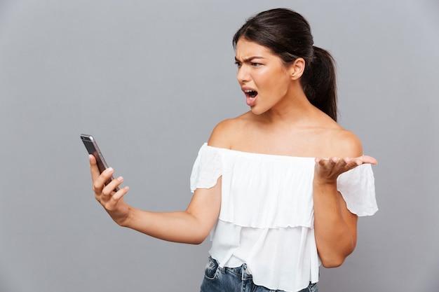 Wütende lässige brünette frau mit smartphone isoliert auf einer grauen wand