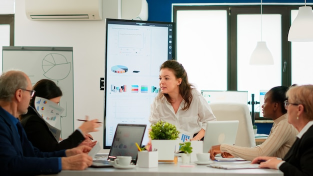 Wütende managerin, die mitarbeiter für schlechtes arbeitsergebnis argumentiert, konferenzraum sitzt, verschiedene kollegen, die verängstigt aussehen. geschäftsfrau, die über multitasking-schwierigkeiten tobt und im sitzungssaal schreit