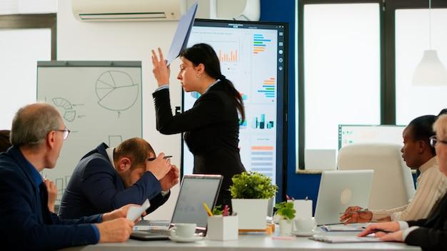 Wütende managerin, die sich über einen schlechten geschäftsvertrag streitet, verschiedene kollegen, die konflikte über das sitzen von dokumenten auf dem schreibtisch während des brainstormings von partnern haben, die im sitzungssaal arbeiten