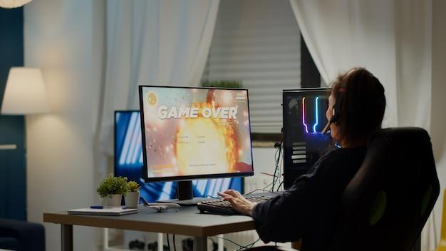 Wütende profi-spielerin mit headset, die ein weltraum-shooter-videospiel mit neuer grafik während der gaming-meisterschaft verliert, die von zu hause aus auf einem leistungsstarken rgb-pc spielt und bei einem esport-turnier auftritt