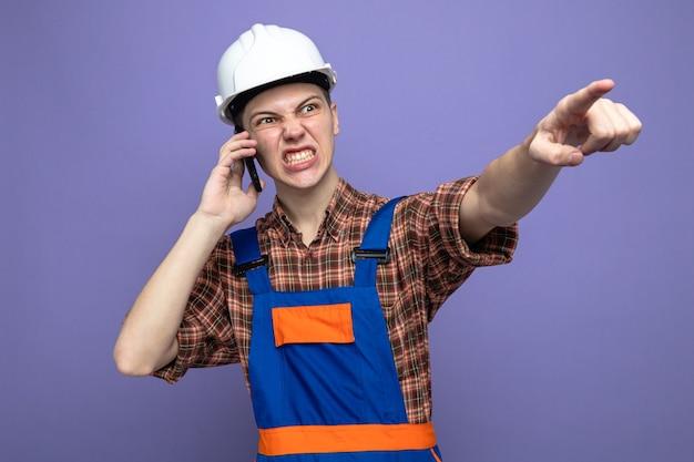 Wütende punkte an der seite junger männlicher baumeister, der uniform trägt, spricht am telefon