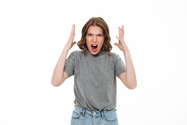 Wütende schreiende junge kaukasische dame, die isoliert steht