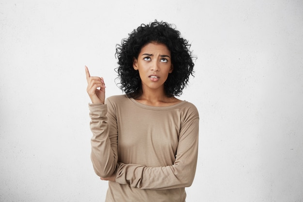 Wütende und empörte junge mischlingsfrau mit afro-frisur, die aufblickt und mit dem zeigefinger nach oben zeigt und sich wütend fühlt, wenn geräusche von nachbarn oben kommen. körpersprache