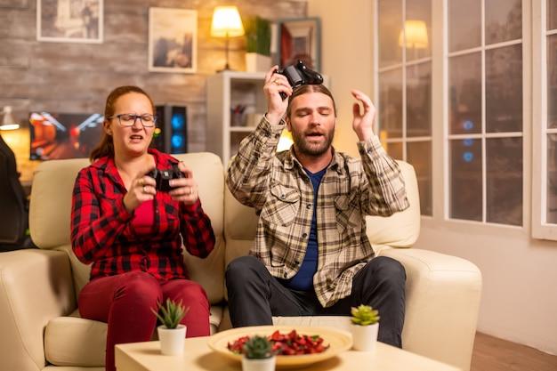Wütende und frustrierte spieler verlieren beim spielen von videospielen spät in der nacht im wohnzimmer