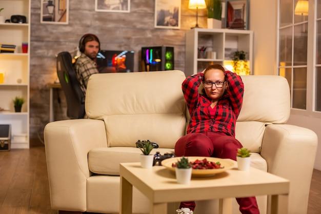 Wütende und frustrierte spielerin, die spät nachts im wohnzimmer videospiele auf der konsole spielt