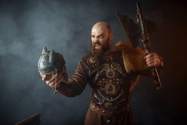Wütende wikinger in traditioneller nordischer kleidung halten den schädel des feindes in helm und axt