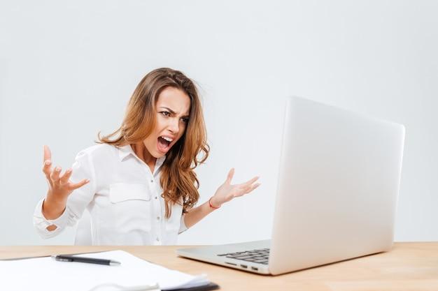 Wütende wütende junge geschäftsfrau, die laptop benutzt und auf weißem hintergrund schreit