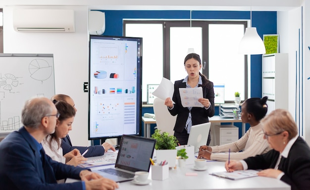 Wütende wütende managerfrau, die im konferenzraum verschiedene firmenmitarbeiter anschreit und sich finanzdiagramme ansieht