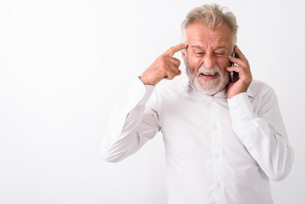 Wütender älterer bärtiger mann, der denkt, während er auf handy auf weiß spricht