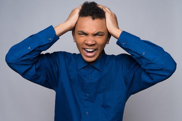 Wütender afroamerikanerjugendlicher greift nach dem kopf.