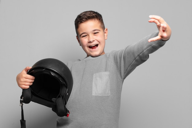 Wütender ausdruck des kleinen jungen. motorradhelmkonzept