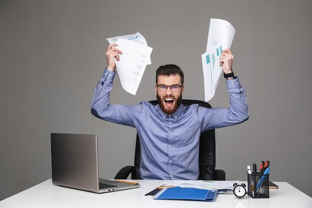 Wütender bärtiger, eleganter mann mit brille, der schreit und direkt schaut, während er dokumente hält, die am tisch im büro sitzen
